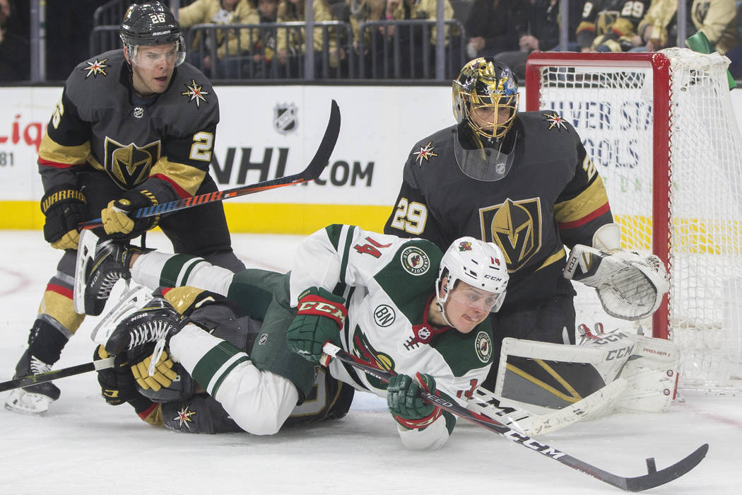 Golden Knights goaltender Marc-Andre Fleury (29) makes a save against Minnesota Wild center Joel Eriksson Ek (14) with the help of Golden Knights center Paul Stastny (26) in the second period on M ...