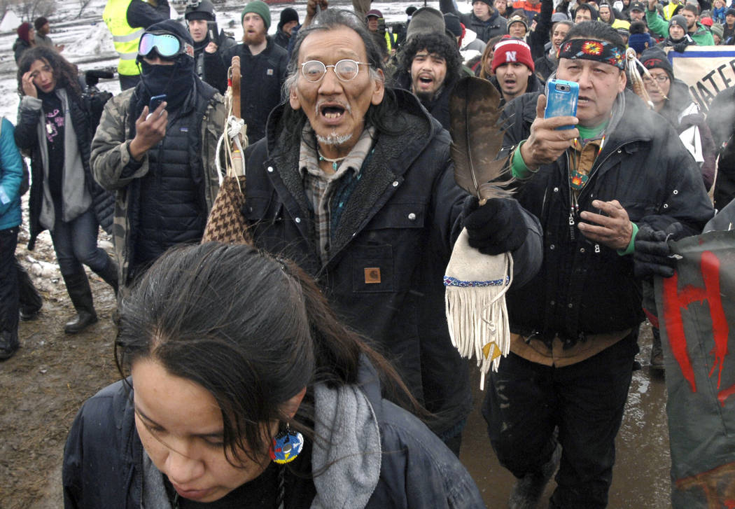 FILE - In this Feb. 22, 2017, file photo, a large crowd representing a majority of the remaining Dakota Access Pipeline protesters, including Nathan Phillips, center with glasses, march out of the ...