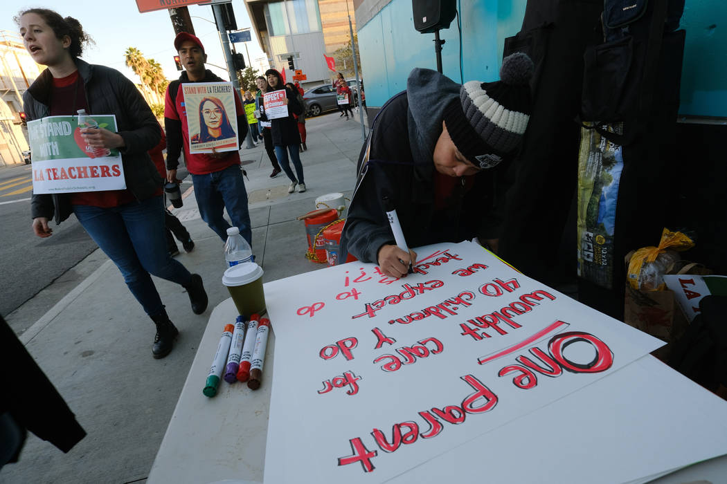 Rosa Companioni prepares a rally sign in support of Los Angeles school teachers Tuesday, Jan. 22, 2019, in Los Angeles. A tentative deal was reached Tuesday, Jan. 22, 2019, between school officia ...
