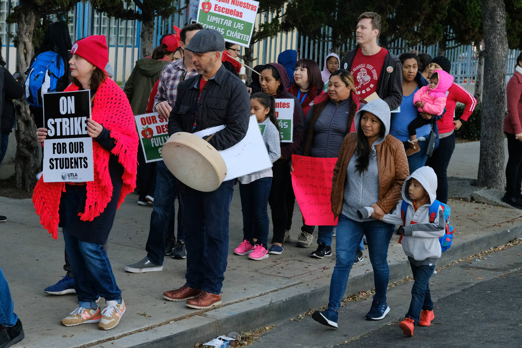 Parents arrive with their children to Evelyn Thurman Gratts Elementary School as people rally in support of Los Angeles school teachers Tuesday, Jan. 22, 2019, in Los Angeles. A tentative deal was ...