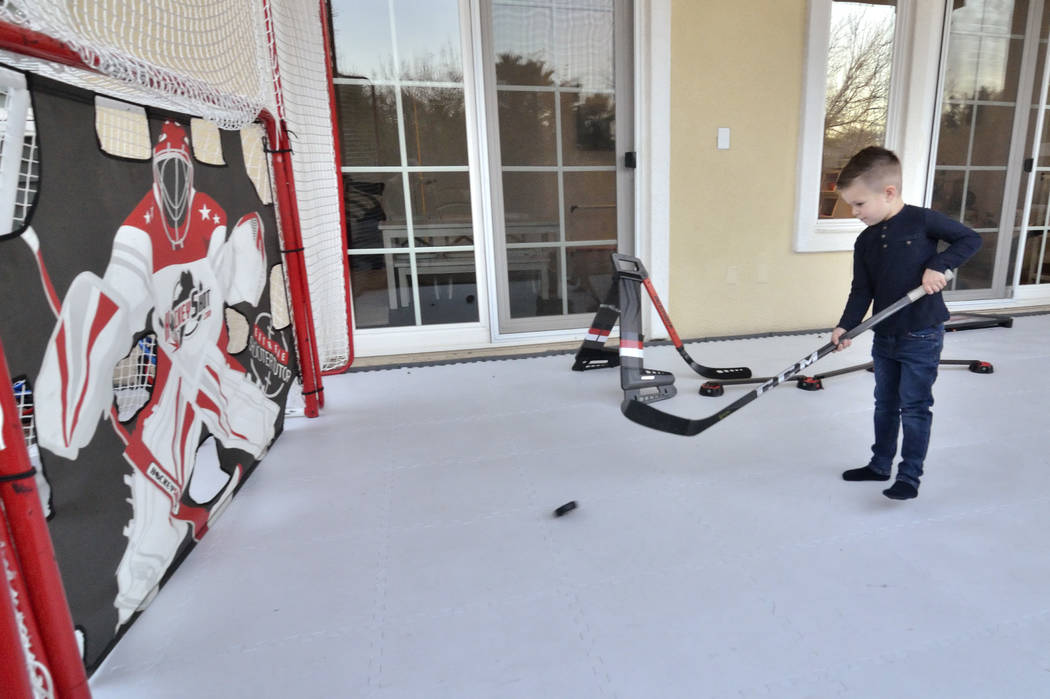 James Marchessault plays on a mini-hockey rink on the patio of his parents home. (Bill Hughes Real Estate Millions)