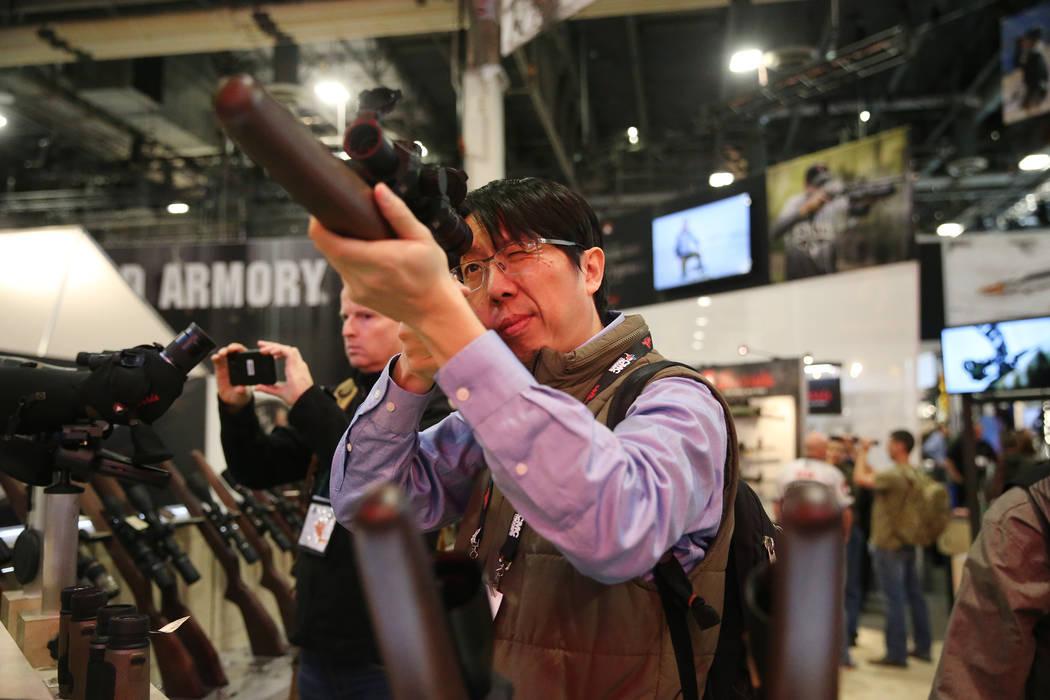 Randy Wei of Taiwan checks out a scope during the SHOT Show at the Sands Expo Convention Center in Las Vegas, Tuesday, Jan. 22, 2019. Erik Verduzco/Las Vegas Review-Journal) @Erik_Verduzco