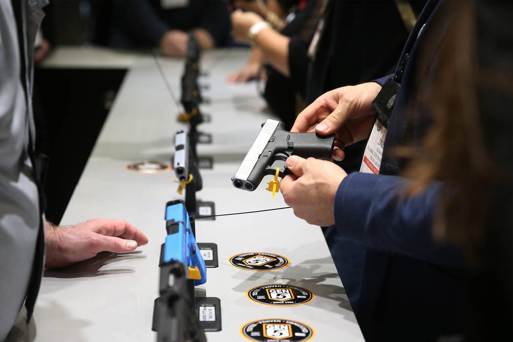 A person checks out a handgun during the SHOT Show at the Sands Expo Convention Center in Las Vegas, Tuesday, Jan. 22, 2019. Erik Verduzco/Las Vegas Review-Journal) @Erik_Verduzco