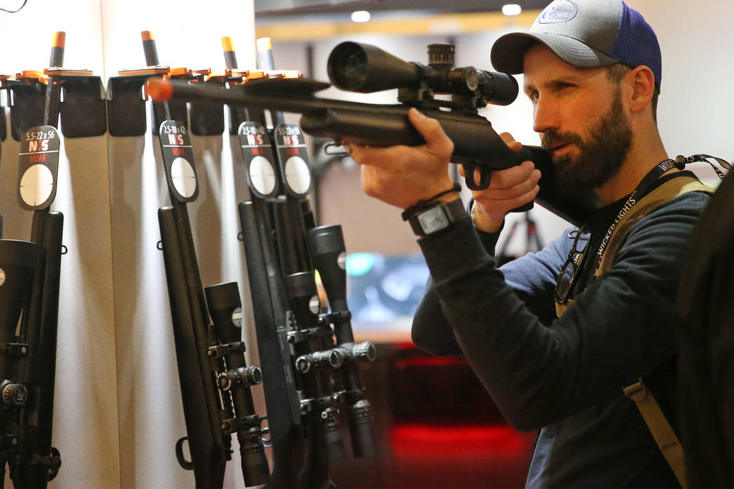Retailer Bryson Gentry of Texas checks out a scope by Nightforce on display during the SHOT Show at the Sands Expo Convention Center in Las Vegas, Tuesday, Jan. 22, 2019. Erik Verduzco/Las Vegas R ...