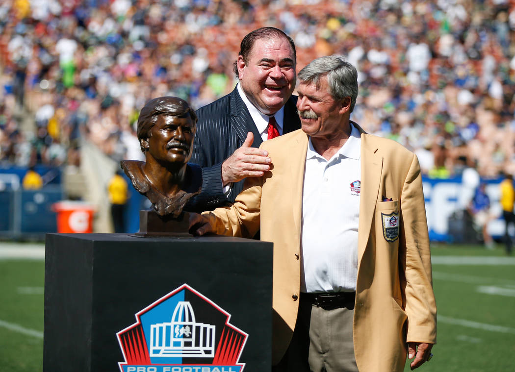 Los Angeles Rams Hall of Famer Tom Mack stands with his bust as Pro Football Hall of Fame President David Baker looks on during the Rams Hall of Fame Ring of Excellence ceremony at halftime of an ...