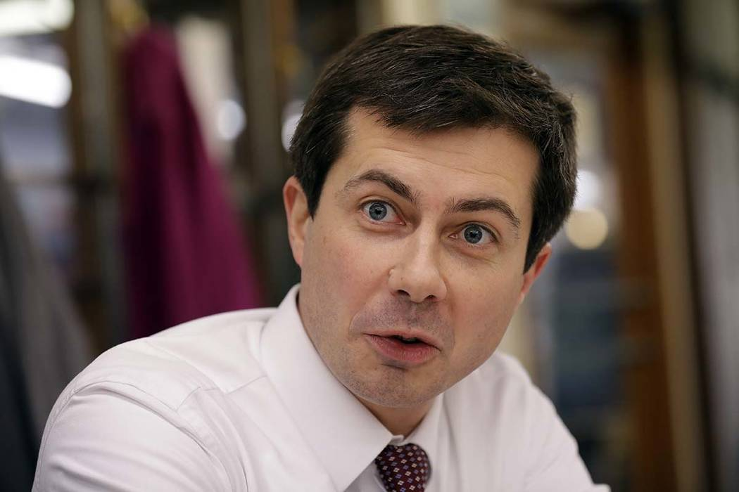 In this Jan. 10, 2019 photo, South Bend, Ind. Mayor Pete Buttigieg, talks with a reporter at Farmers Market in South Bend, Ind. (AP Photo/Nam Y. Huh)