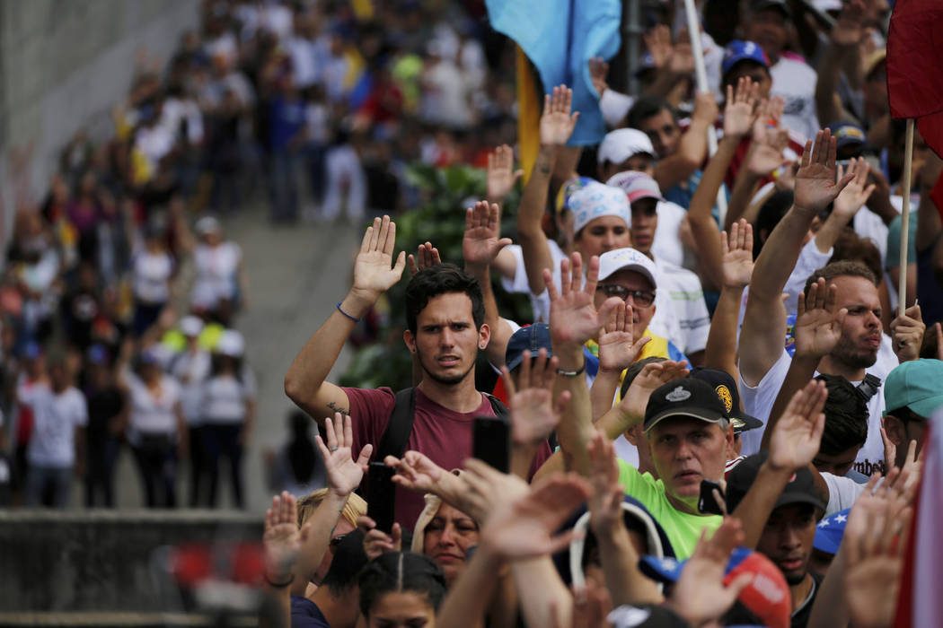 Anti-government protesters hold their hands up during the symbolic swearing-in of Juan Guaido, head of the opposition-run congress, who declared himself interim president of Venezuela, during a ra ...