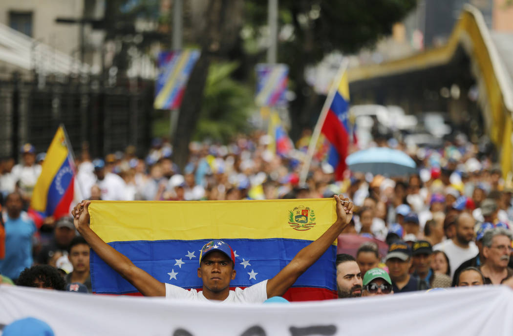 An opposition member holds a Venezuelan national flag during a protest march against President Nicolas Maduro in Caracas, Venezuela, Wednesday, Jan. 23, 2019. (Fernando Llano/AP)