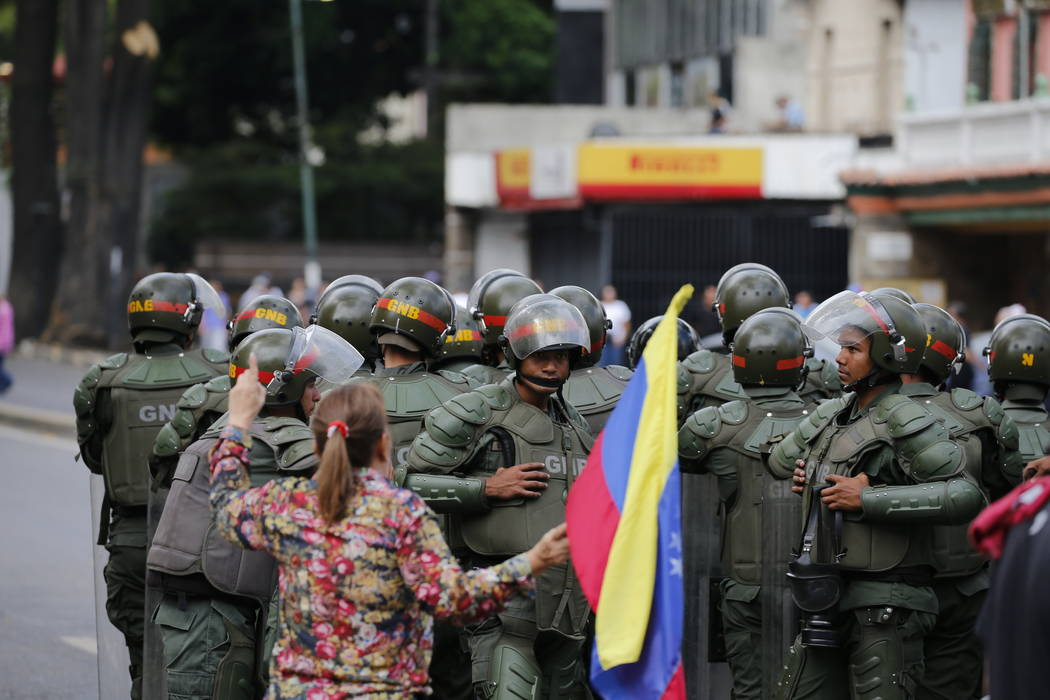 A woman holding a Venezuelan national flag heckles Bolivarian National Guardsmen blocking the passage of opposition members during a protest march against President Nicolas Maduro in Caracas, Vene ...