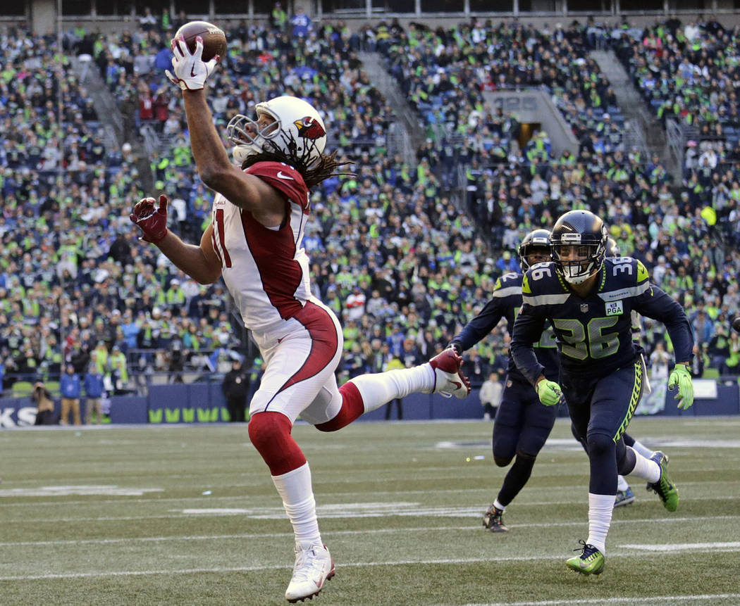 In this Dec. 30, 2018, file photo, Arizona Cardinals' Larry Fitzgerald, left, snags a one-handed touchdown pass against the Seattle Seahawks during the first half of an NFL football game, in Seatt ...