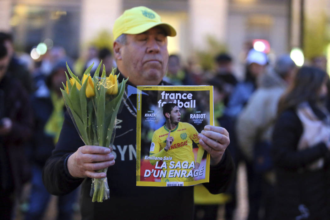 A FC Nantes soccer fan displays the cover of French soccer magazine, France Football, featuring FC Nantes soccer player Emiliano Sala of Argentina, during a tribute in Nantes, western France, Tues ...