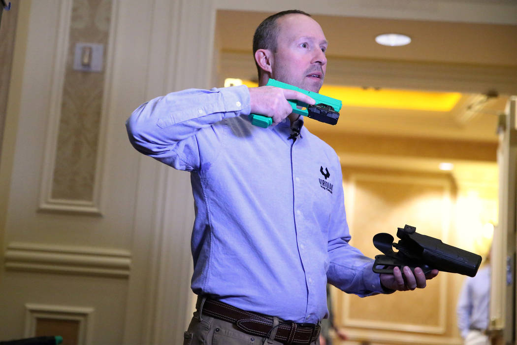 Brian Hedeen, president and CEO of Viridian Weapon Technologies, gives a demonstration of their weapon mounted camera during the SHOT Show at the Sands Expo Convention Center in Las Vegas, Wednesd ...