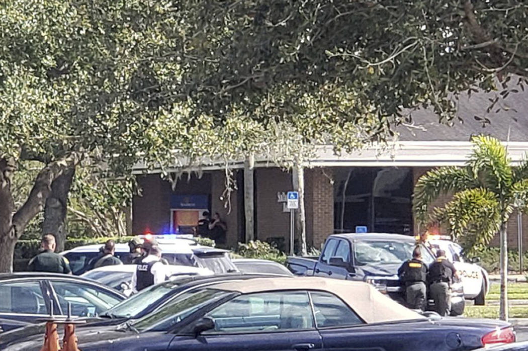 Law enforcement officials take cover outside a SunTrust Bank branch, Wednesday, Jan. 23, 2019, in Sebring, Fla. Authorities say they've arrested a man who fired shots inside the Florida bank. (The ...