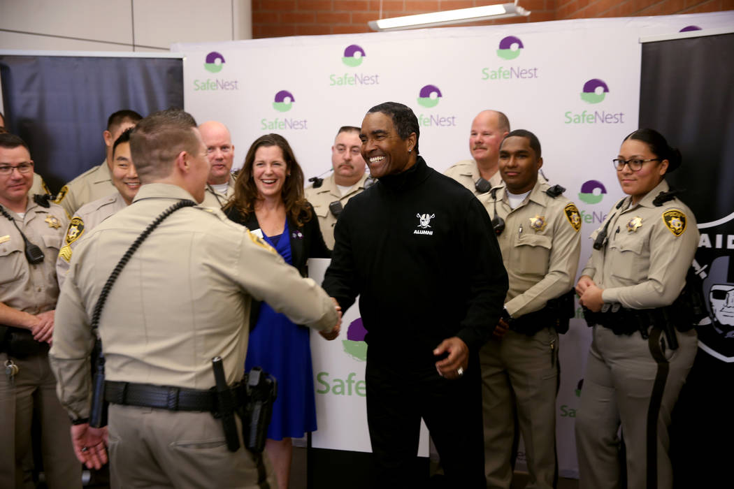 Raiders alumnus Leo Gray shakes hands with Las Vegas police Lt. Timothy Hatchett at SafeNest headquarters in Las Vegas on Thursday, Jan. 24, 2019. Hatchett initiated Project Safe 417, a partnershi ...