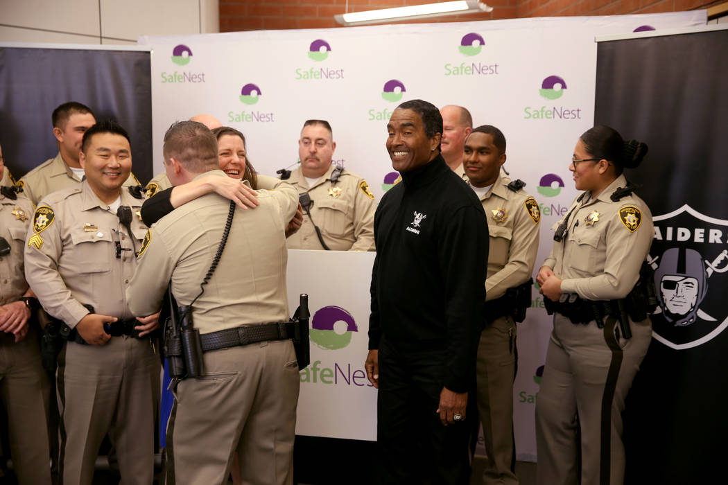 SafeNest CEO Liz Ortenburger hugs Las Vegas police Lt. Timothy Hatchett as Raiders alumnus Leo Gray looks on at SafeNest headquarters in Las Vegas on Thursday, Jan. 24, 2019. Hatchett initiated Pr ...