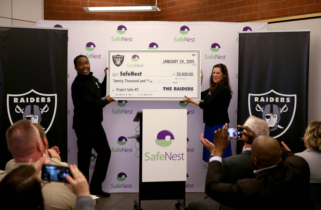 Raiders alumnus Leo Gray presents SafeNest CEO Liz Ortenburger with a check at SafeNest headquarters in Las Vegas on Thursday, Jan. 24, 2019. The money will help fund Project Safe 417, a partnersh ...