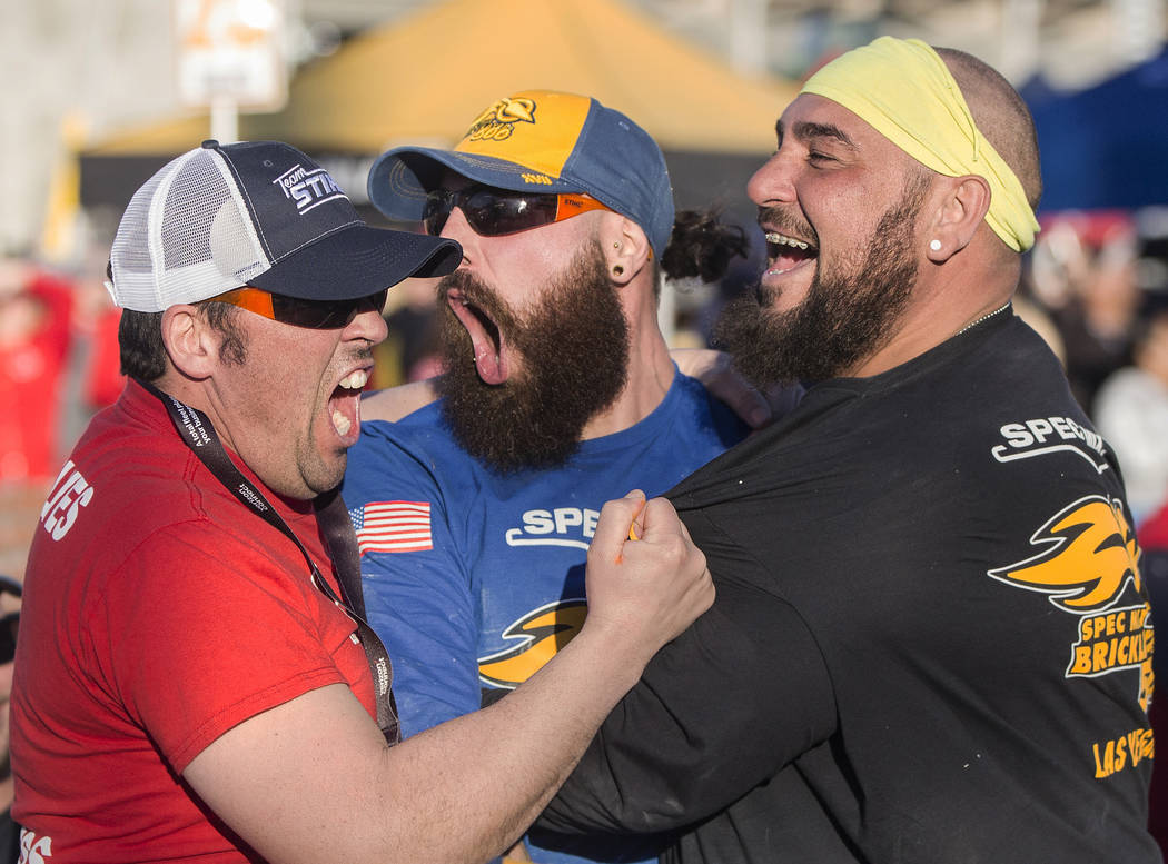 Mario Alves, middle, from Hamilton, Ontario, celebrates with teammate and brother Michael Alves, right, after winning the Spec Mix Bricklayer 500 during day two of the World of Concrete trade show ...