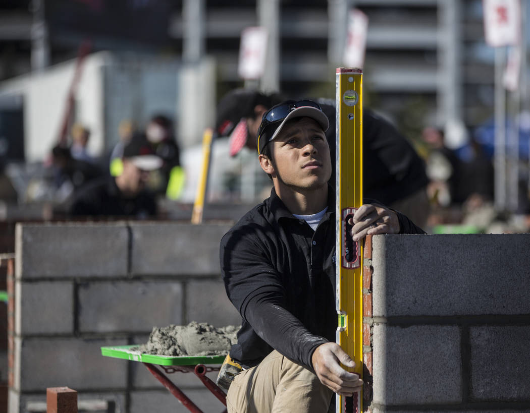 Mason Temple, with Stoney Masonry, uses a level to measure his wall during a masonry competition during day two of the World of Concrete trade show on Wednesday, Jan. 23, 2019, at the Las Vegas Co ...