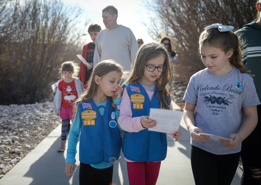 Sofia Burkhead, 5, left, Raquel Burkhead, 6, and Rae Puckett, 8, look at a diagram with various types of birds as they go on a walk as part of the Young Explorers event at the Las Vegas Wetlands P ...