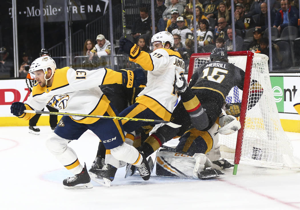 Golden Knights defenseman Jon Merrill (15) falls into the net of Nashville Predators goaltender Juuse Saros (74) during the second period of an NHL hockey game at T-Mobile Arena in Las Vegas on We ...