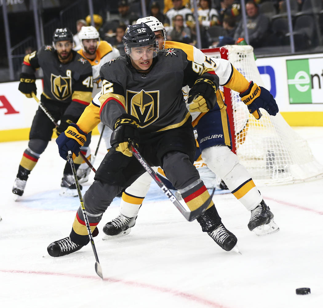Golden Knights left wing Tomas Nosek (92) chases after a loose puck in front of Nashville Predators defenseman Dan Hamhuis (5) during the second period of an NHL hockey game at T-Mobile Arena in L ...