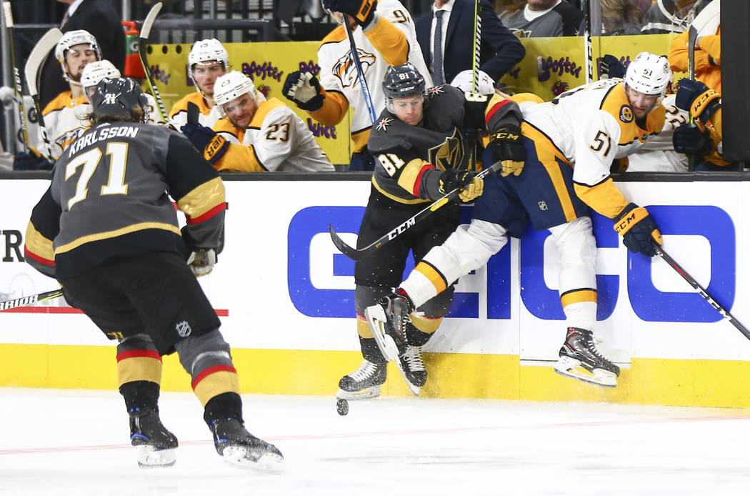 Golden Knights center Jonathan Marchessault (81) and Nashville Predators left wing Austin Watson (51) battle for a loose puck during the third period of an NHL hockey game at T-Mobile Arena in Las ...
