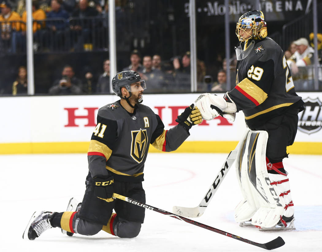 Golden Knights center Pierre-Edouard Bellemare (41) fist bumps Golden Knights goaltender Marc-Andre Fleury (29) during the third period of an NHL hockey game against the Nashville Predators at T-M ...