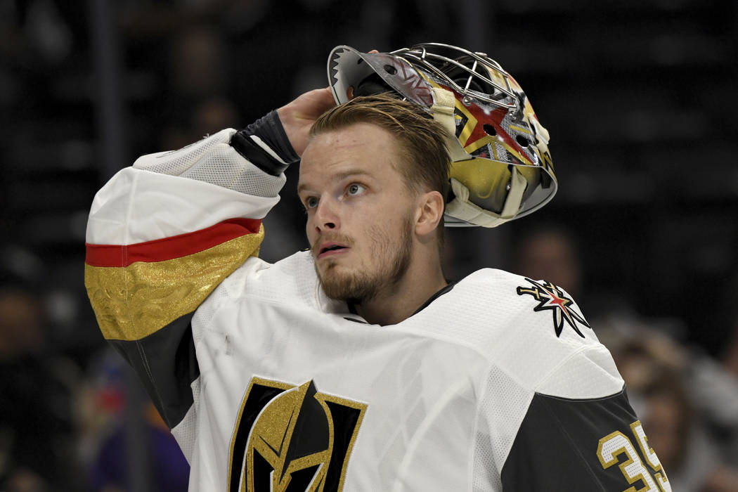 Vegas Golden Knights goalie Oscar Dansk, of Sweden, puts on his mask before a preseason NHL hockey game against the Los Angeles Kings, Thursday, Sept. 20, 2018, in Los Angeles. (AP Photo/Michael O ...