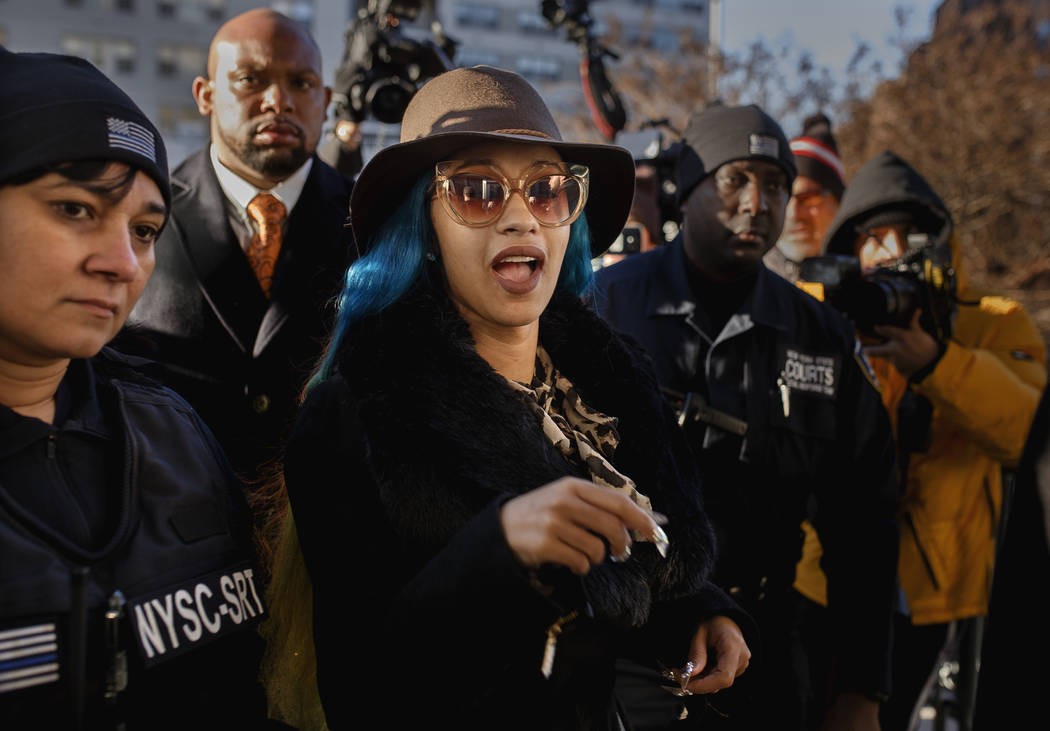 Rapper Cardi B, center, arrives at Queens County Criminal Court, Friday, Dec. 7, 2018, in New York. The platinum-selling hip hop star is scheduled to appear in court on charges related to a braw ...