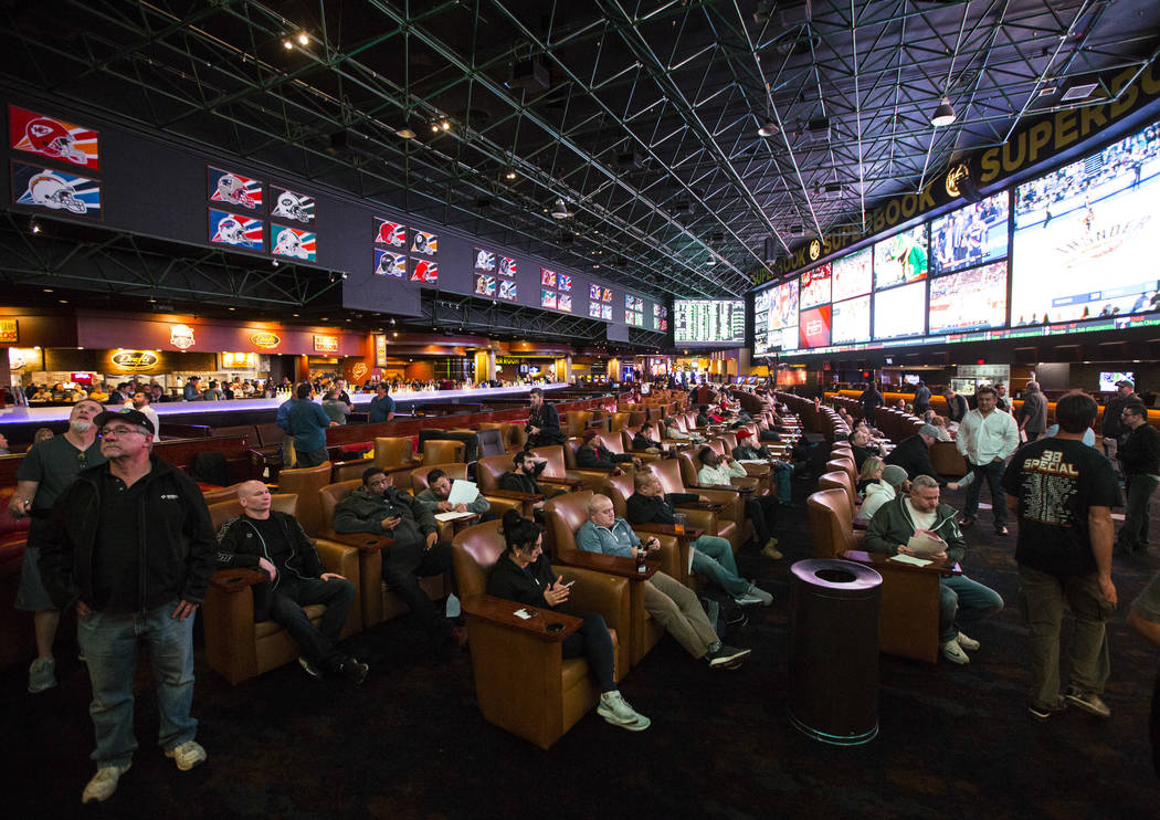 Bettors look at the displays of prop bets for the Super Bowl at the Westgate Superbook in Las Vegas on Thursday, Jan. 24, 2019. The sportsbook posted 442 two-way props and more than 1,000 betting ...
