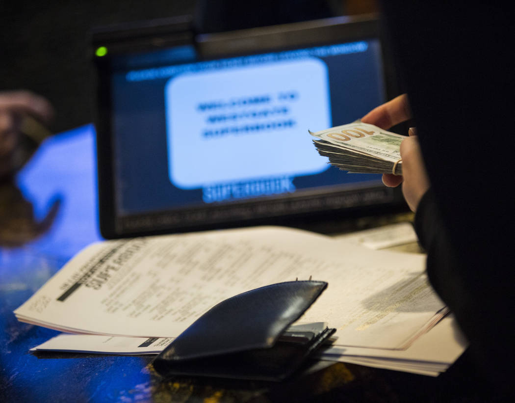 A bettor from Singapore takes out cash to place prop bets for the Super Bowl at the Westgate Superbook in Las Vegas on Thursday, Jan. 24, 2019. The sportsbook posted 442 two-way props and more tha ...