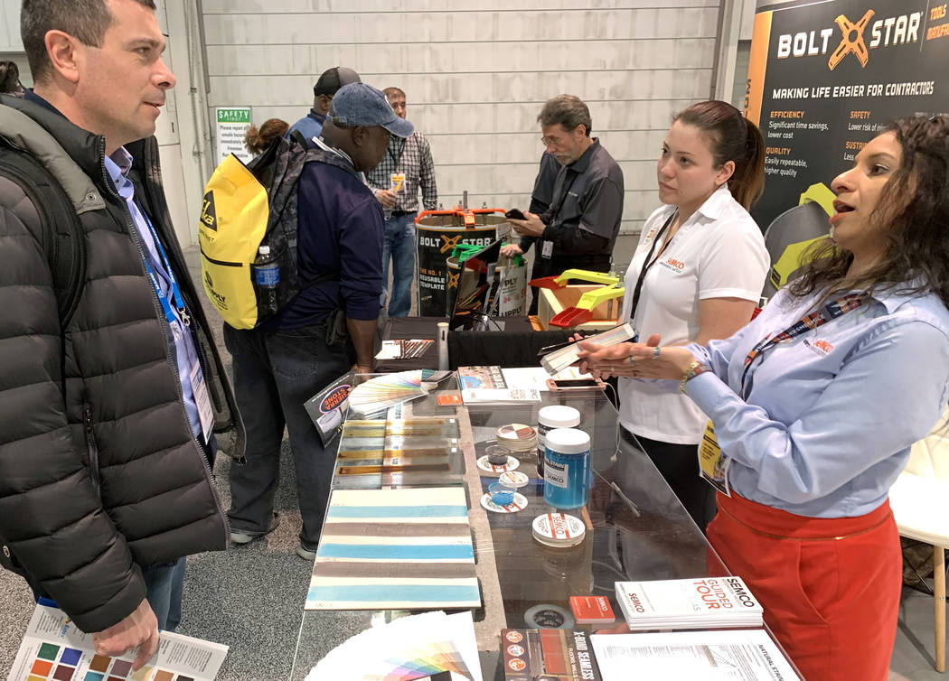Sona Shah, national project integrator at Semco Modern Seamless Surface, right, and Fran Campos talk to Alessandro Fenini of Italy in their booth at the World of Concrete trade show at the Las Veg ...