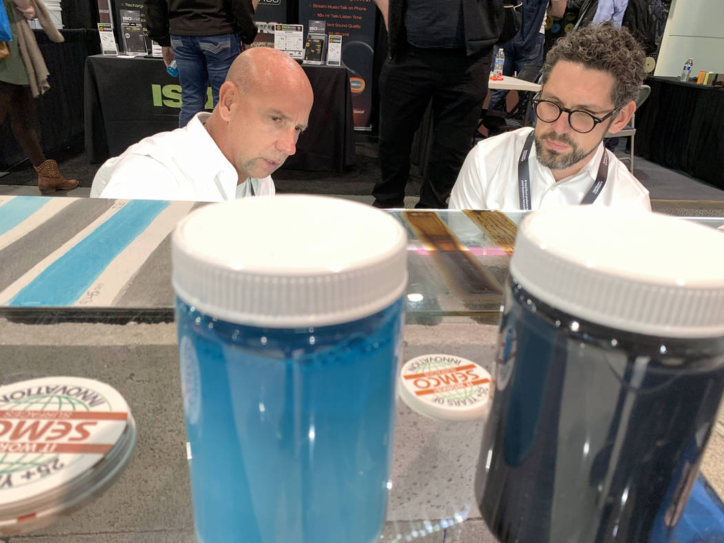 Adam Nitte with Semco Modern Seamless Surface, right, talks to Robert Polo of Valencia, California, at his booth at the World of Concrete trade show at the Las Vegas Convention Center Thursday, Ja ...