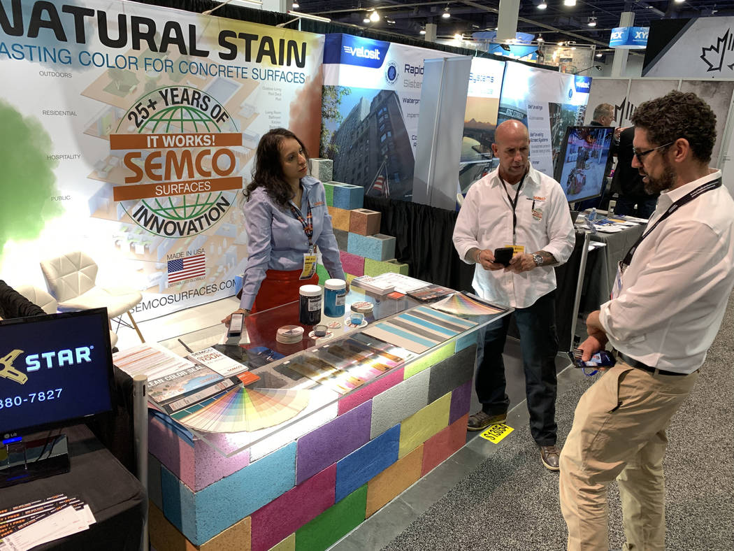 Sona Shah, national project integrator at Semco Modern Seamless Surface, left, and Adam Nitte talk to Robert Polo of Valencia, California in their booth at the World of Concrete trade show at the ...