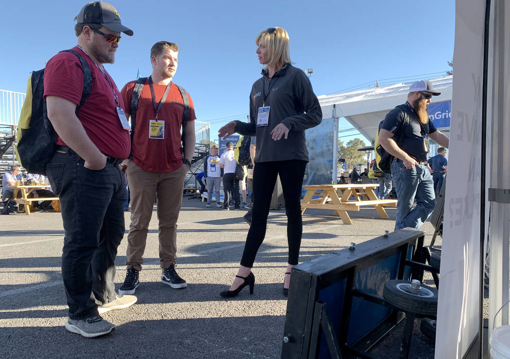 Krista Waddell, president of ART Concrete Solutions, talks to Kyle Loy, left, and Dugan Herrick of Pittsburg, Kansas at her booth at the World of Concrete trade show at the Las Vegas Convention Ce ...