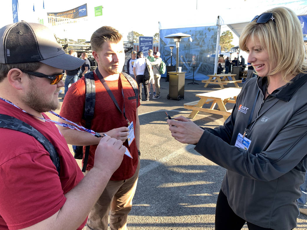 Krista Waddell, president of ART Concrete Solutions, scans badges of Kyle Loy, left, and Dugan Herrick of Pittsburg, Kansas at her booth at the World of Concrete trade show at the Las Vegas Conven ...