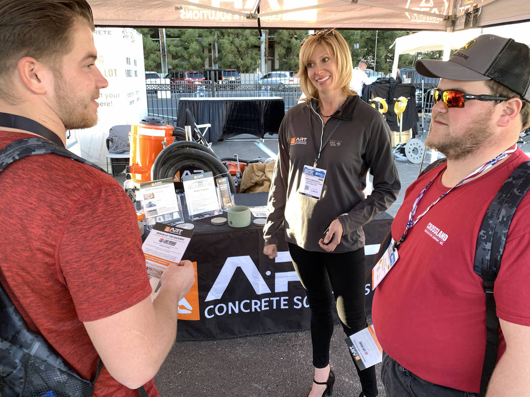 Krista Waddell, president of ART Concrete Solutions, talks to Dugan Herrick, left, and Kyle Loy of Pittsburg, Kansas at her booth at the World of Concrete trade show at the Las Vegas Convention Ce ...