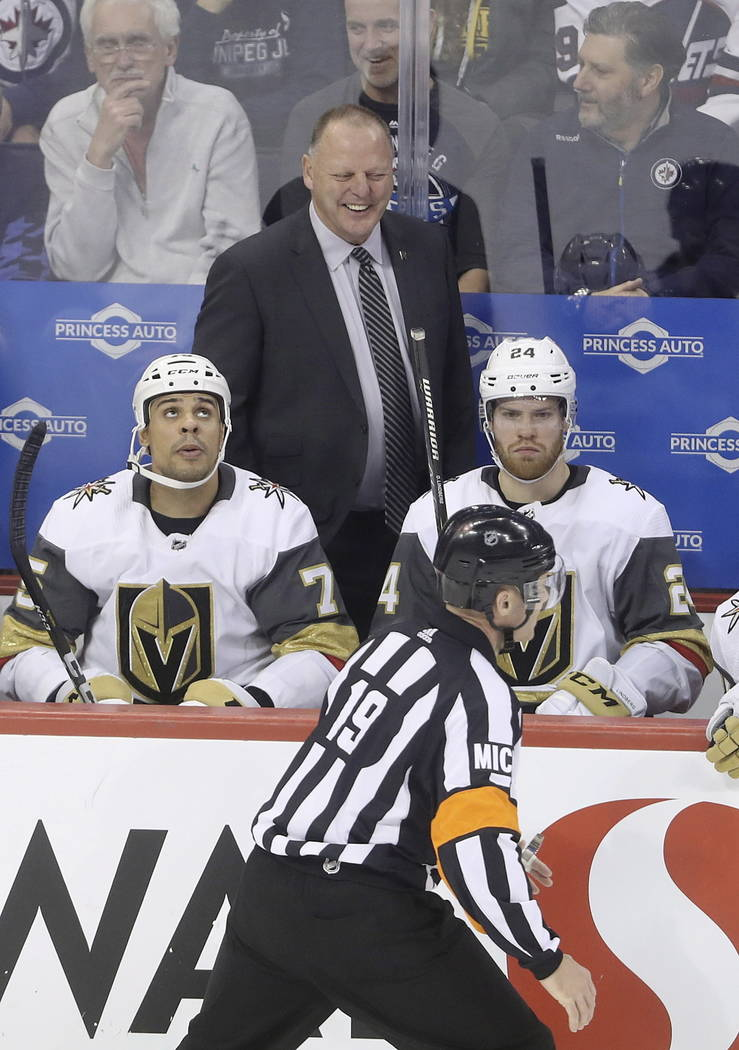 Referee Gord Dwyer (19) talks to a laughing Vegas Golden Knights coach Gerard Gallant after Dwyer and a linesman cleared a buildup of snow from the crease when the Knights pulled goaltender Marc-A ...