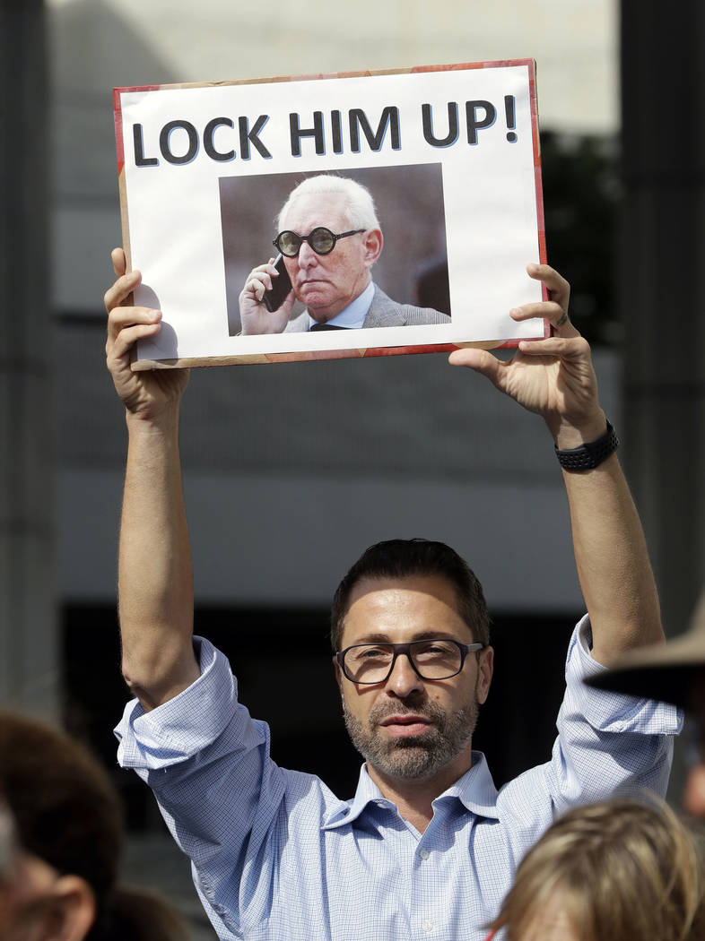 A protestor holds a sign depicting Roger Stone, a confidant of President Donald Trump, as Stone attends a hearing at the federal courthouse following a hearing, Friday, Jan. 25, 2019, in Fort Laud ...