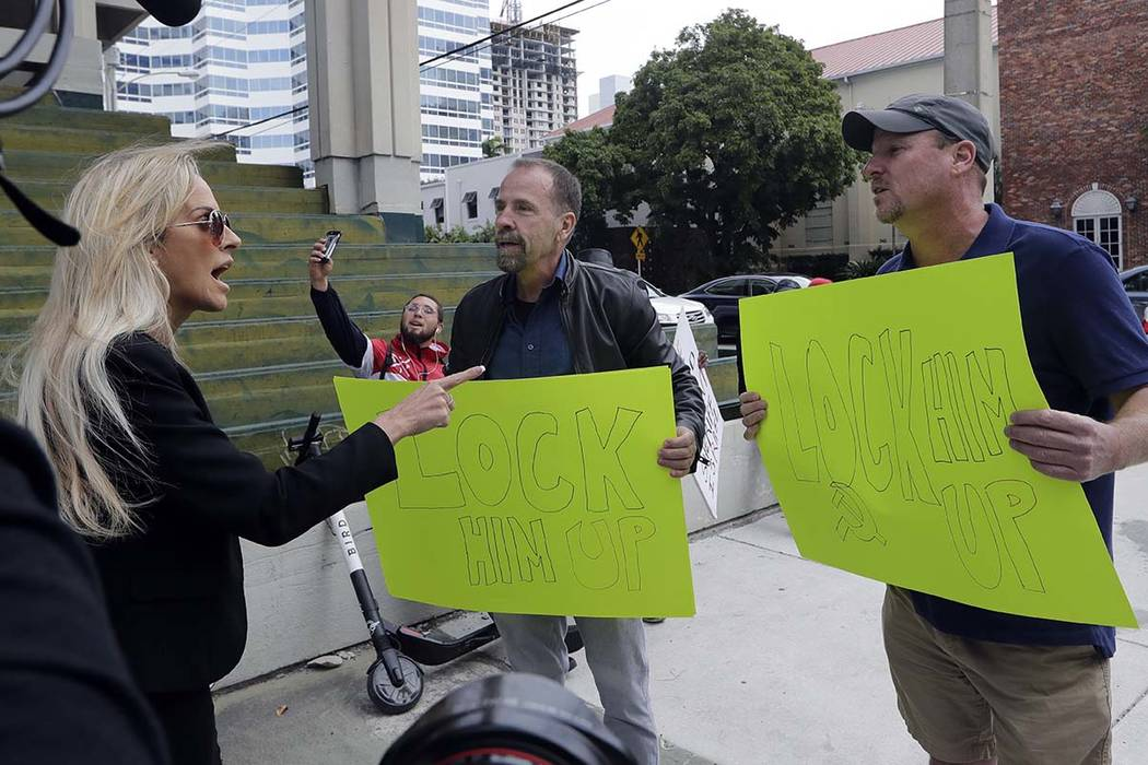 """People holding signs reading """"Lock Him Up"""" argue with a counter protestor outside of the federal courthouse where Roger Stone, a confidant of President Donald Trump, has a hearing, Friday, Jan. 25 ..."""