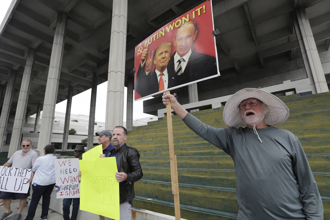 Bob Welsh, of South Miami, Fla., holds a sign outside of the federal courthouse where there is a hearing for Roger Stone, a confidant of President Donald Trump, Friday, Jan. 25, 2019, in Fort Laud ...