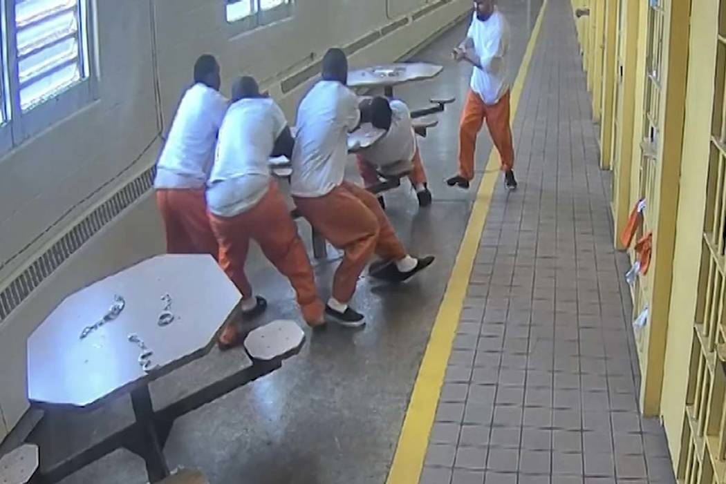 In this screenshot taken from a Southern Ohio Correction Facility security camera video four inmates, handcuffed to a table, are attacked by a fellow prisoner who slipped his handcuffs and brandis ...