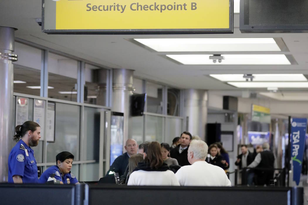 Passengers stand in line as they wait to pass through a TSA security checkpoint at LaGuardia airport Monday, Jan. 7, 2019, in New York. (AP Photo/Frank Franklin II)