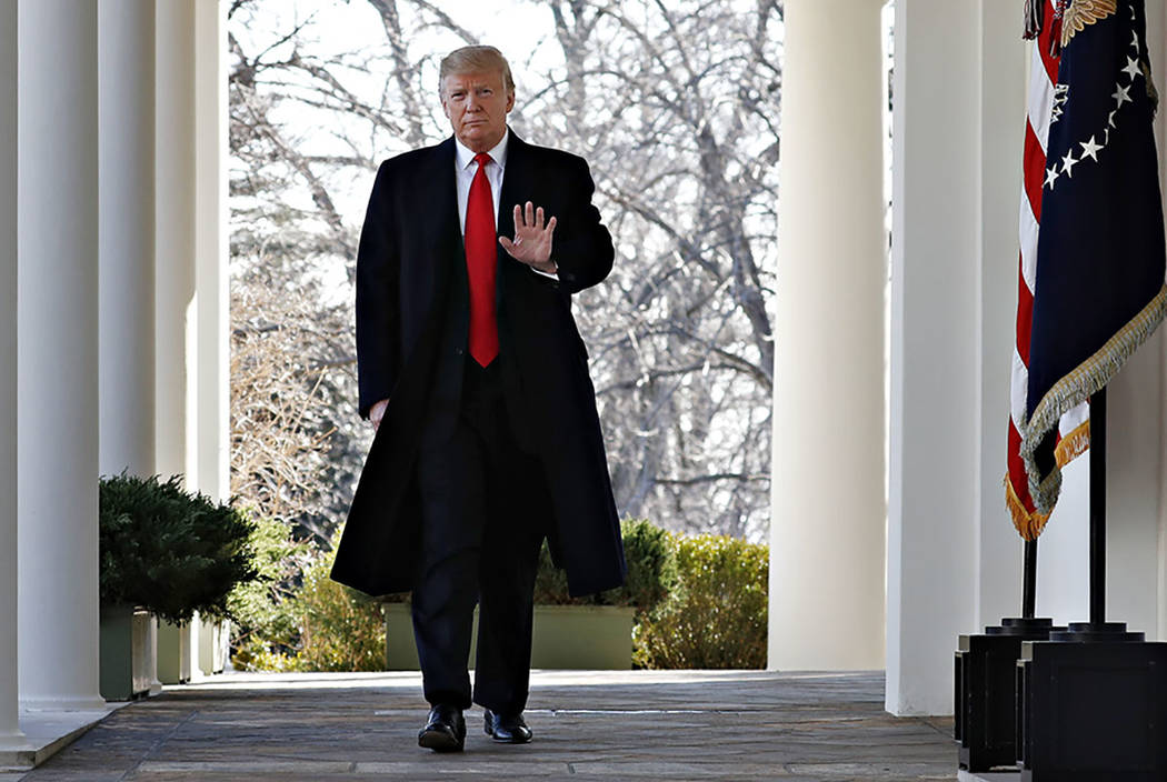 President Donald Trump waves as he walks through the Colonnade from the Oval Office of the White House on arrival to announce a deal to temporarily reopen the government, Friday, Jan. 25, 2019, fr ...