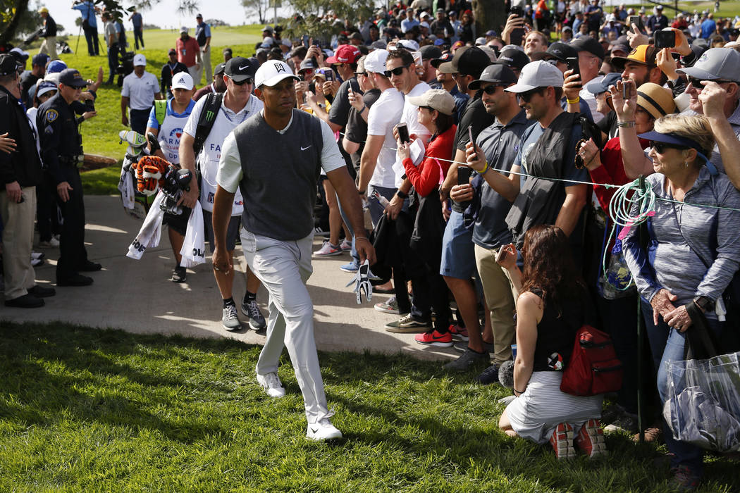Tiger Woods passes a crowd as he makes his way to the seventh hole of the South Course at Torrey Pines during the first round of the Farmers Insurance golf tournament Thursday, Jan. 24, 2019, in S ...