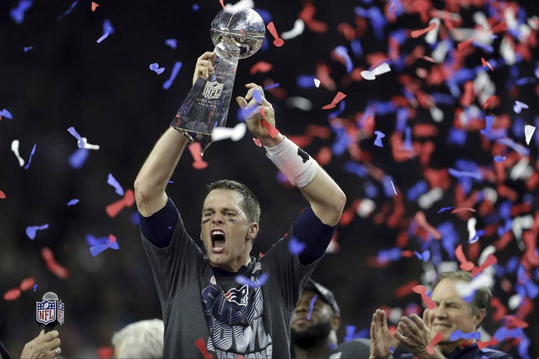 In this Feb. 5, 2017, file photo, New England Patriots' Tom Brady raises the Vince Lombardi Trophy after defeating the Atlanta Falcons in overtime at the NFL Super Bowl 51 football game, in Housto ...