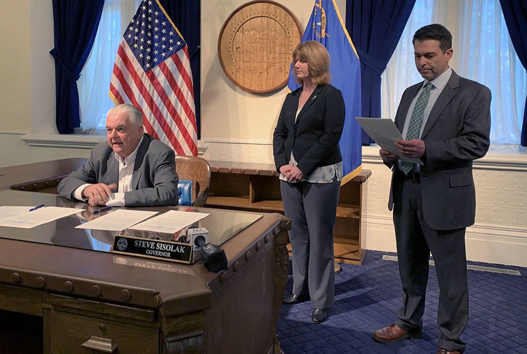 Gov. Steve Sisolak speaks Friday after signing an order creating an advisory panel to draft legislation for Cannabis Compliance Board to regulate the state's marijuana industry. To his left are Me ...