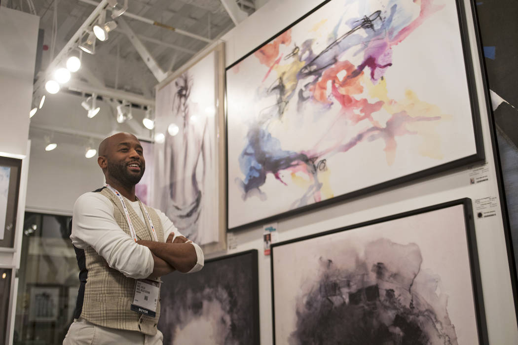 Interior designer Mikel Welch stands by his picks of abstract art by artist Kari Taylor at the Daleno showroom at the Las Vegas Winter Market at World Market Center in Las Vegas, Sunday, Jan. 27, ...