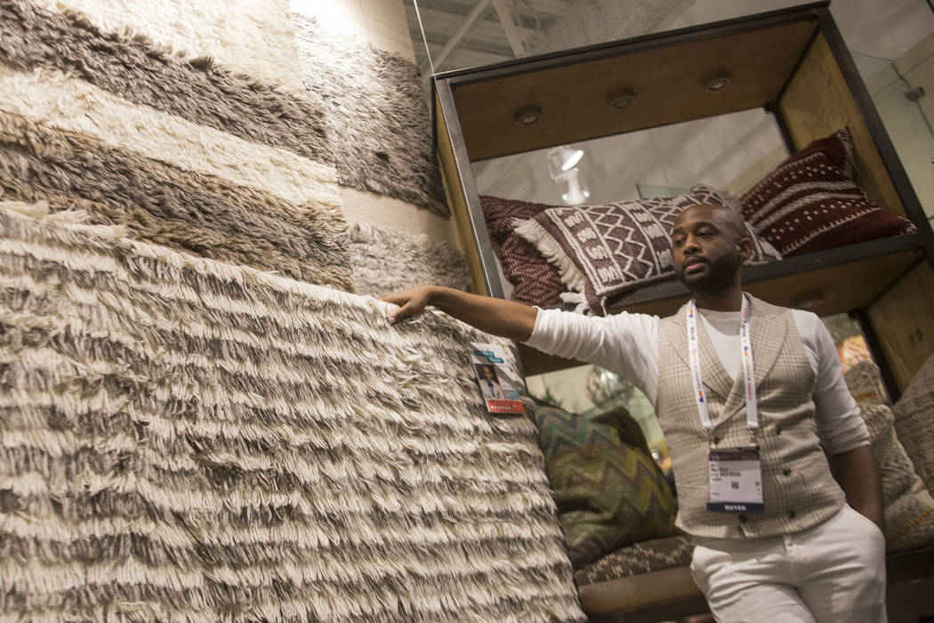 Interior designer Mikel Welch points out neutral rugs that are a part of the Abbot Collection by Ellen DeGeneres at the Loloi showroom on Tour the Trends at the Las Vegas Winter Market at World Ma ...