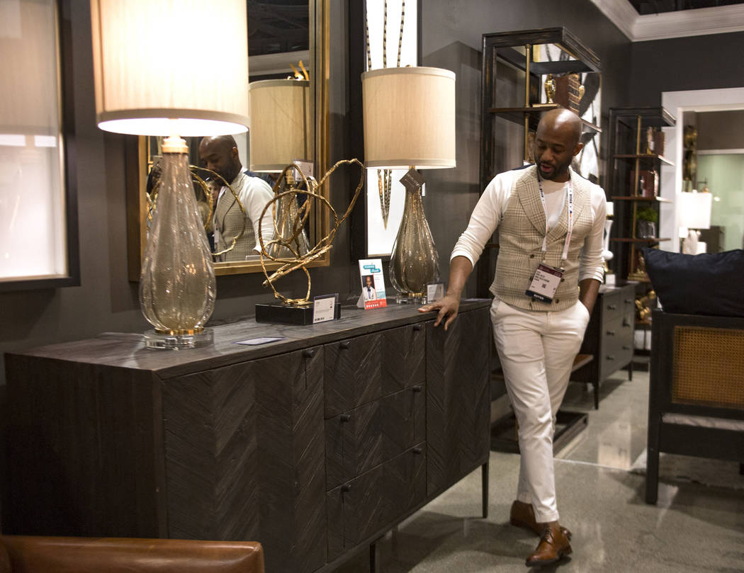 Interior designer Mikel Welch points out a gray cabinet with a black finish at the Revelation by Uttermost showroom on Tour the Trends at the Las Vegas Winter Market at World Market Center in Las ...
